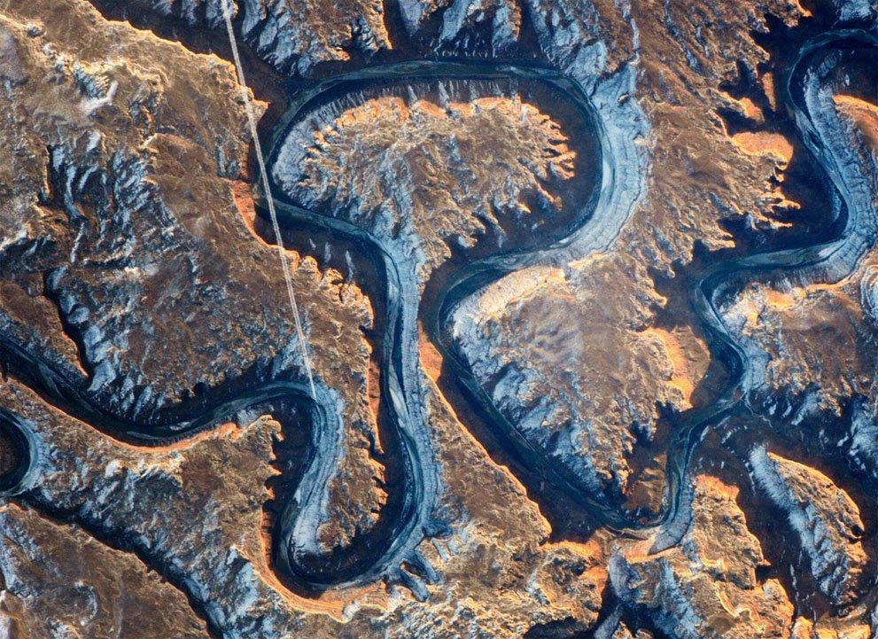این بخش از دره رودخانه سبز (رود کلرادو) در شرق یوتا به خاطر نمای پیچ در پیچش مشهور است. این عکس در ۲۲ ژانویه ۲۰۱۴ توسط فضانوردی در ایستگاه بین المللی گرفته شده. رودخانه سبز به خاطر سایه های عمیق، تیره به نظر می رسد زیرا ۳۰۰ متر پایین تر از سطح زمین های اطراف خود است. نور خورشید در حال طلوع که بخشی از دیواره های دره را روشن کرده نیز زیبا است. خط صافی که در نیمه سمت چپ عکس دیده می شود، خط پرواز یک جت بر فراز دره است.