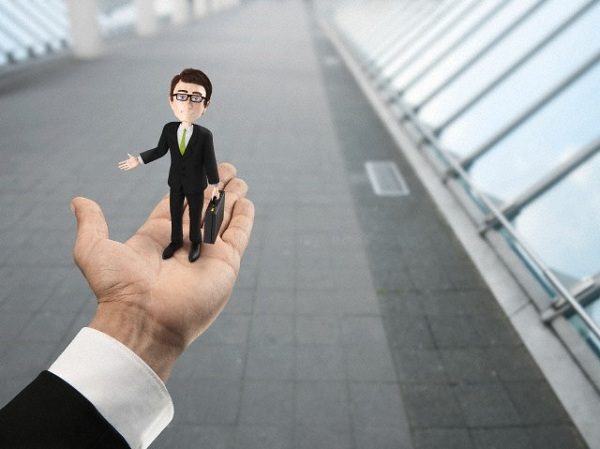 Hand holding businessman figurine