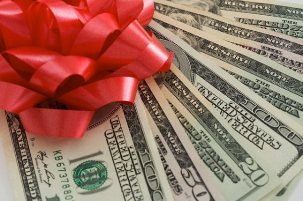 Close-up of dollars with gift bow