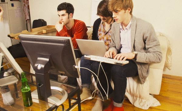 Three young men working on computers on their living room sofa