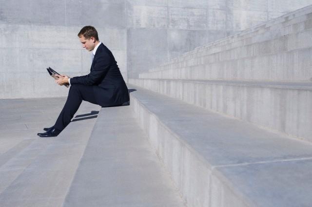 Businessman sitting on concrete steps using digital tablet