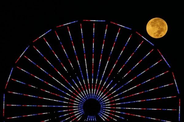 ماه، پس از ماه گرفتگی کاملی که در 8 اکتبر 2014 روی داد، پشت این چرخ و فلک دیده می شود. رنگ ماه که به سرخی می گراید، به دلیل قرار گرفتن در سایه زمین است. این رویداد به نام «ماه خونین» نیز معروف است.
