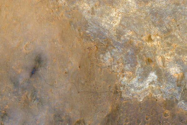 در گوشه پایین سمت راست می توانید یک نقطه نورانی را مشاهده نمایید که همان کاوشگر Curiosity ناساست و درست پشت سر آن هم ردی را مشاهده می کنید که در اثر حرکت آن روی سطح خاکی ایجاد شده.