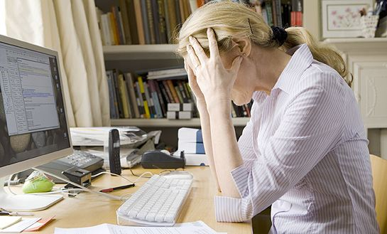 stress woman in office at desk