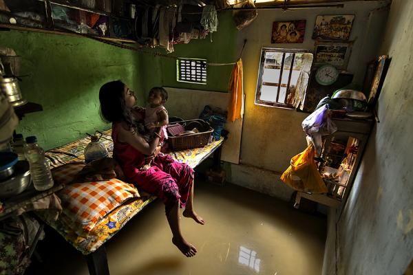 برنده شاخه مردم؛ مادری در حال بازی با فرزندش در اتاقی که آب کف آن را فرا گرفته. این عکس در کلکته هند شکار شده است.