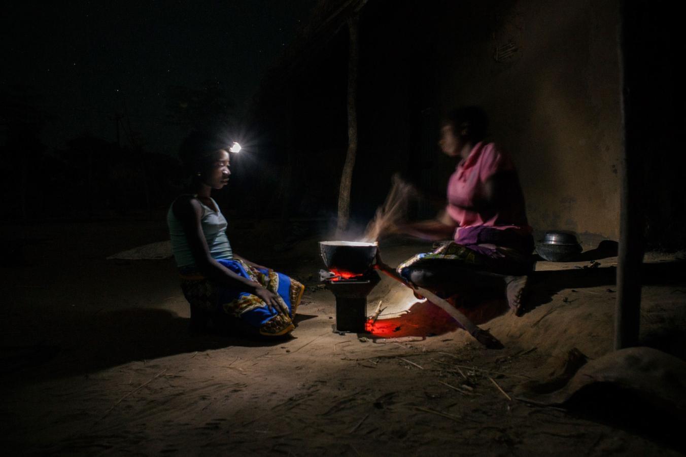 هنگامی که برق نباشد، با غروب خورشید ساده ترین کارها به دشوار ترین فعالیت ها تبدیل می شوند. در این عکس مادر و دختری با چراغ قوه مشغول پخت و پز هستند.