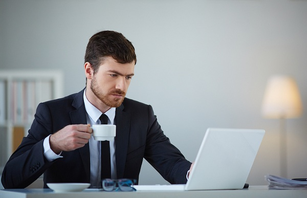 Handsome businessman using laptop and having tea or coffee in office