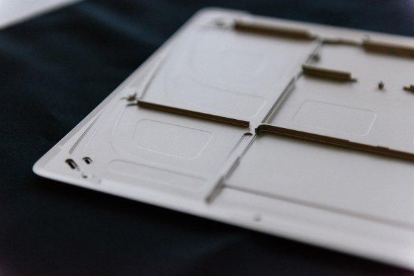 قاب پشتی مک بوک که از آلومینیوم تهیه شده و می توان فضایی که قرار است با باتری پر شود را در آن مشاهده کرد.