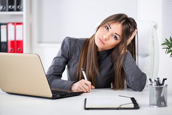 Worried Businesswoman in the office, sitting and thinking about problems. Looking at camera.