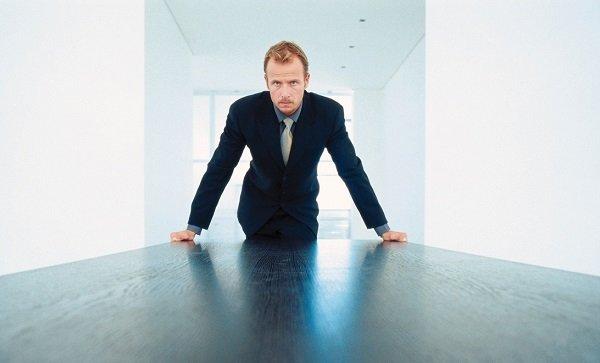 Man-in-Board-room-Looking-Length-of-Desk-MP900422602