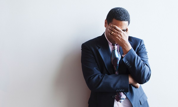 CMN7BH African American businessman leaning against wall covering his face