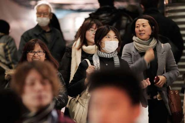 TOKYO, JAPAN - FEBRUARY 13: Commuters in Tokyo wear surgical masks to help protect themselves from the influenza outbreak on February 13, 2012 in Tokyo, Japan. As the number of influenza patients is reported to have reached 2 million in Japan, Japanese passengers were quarantined by New Zealand authorities on an incoming flight at Auckland airport on monday after they displayed flu like symptoms. (Photo by Adam Pretty/Getty Images)