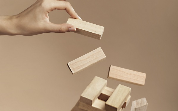 hand holding a wooden block while the rest fall