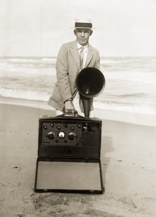 ca. 1923 --- Edward Howard Armstrong of New York, known as the radio millionaire daredevil, cannot forsake his radio. He is shown here on the beach, with a six-bulb suit case receiver. Armstrong is the inventor of the regenerative principle, which revolutionized radio reception and transmission, and made radio broadcasting possible. --- Image by © AS400 DB/Corbis