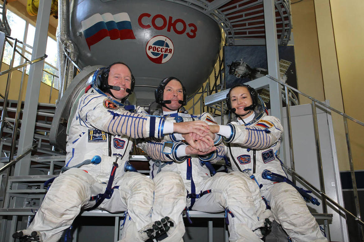 2094: At the Gagarin Cosmonaut Training Center in Star City, Russia, Expedition 41/42 prime crewmembers Barry Wilmore of NASA (left), Alexander Samokutyaev of the Russian Federal Space Agency (Roscosmos, center) and Elena Serova of Roscosmos (right) clasp hands during a photo opportunity September 4 at the start of the second day of final qualification exams. The trio will launch from the Baikonur Cosmodrome in Kazakhstan, Sept. 26, Kazakh time, in their Soyuz TMA-14M spacecraft for a 5 ½ month mission on the International Space Station. Serova will become the fourth Russian woman to fly in space and the first Russian woman to conduct a long duration mission on the station. NASA/Stephanie Stoll