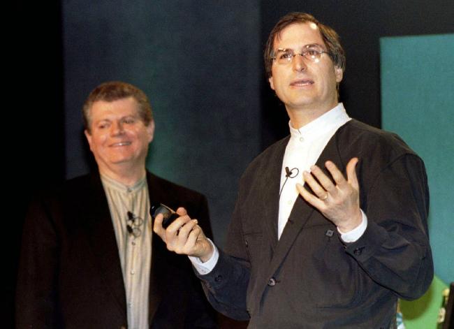 در انتهای دهه ۹۰ میلادی، کار اپل در حال تمام شدن بود. پس از رفتن «جان اسکالی» از کوپرتینو، آقای «گیل آملیو» (Gil Amelio) برای مدت کوتاهی عنوان مدیر عاملی اپل را در دست گرفت. مدیر عامل وقت اپل، آقای آملیو تصمیم گرفتNeXT را بخرد و جابز را به اپل برگرداند تا بلکه این کمپانی نجات پیدا کند. گیتس اما تمام تلاش خود را کرد تا آملیو را از این تصمیم منصرف کند.