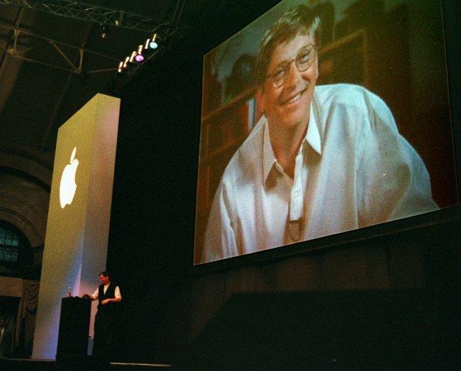 در سال ۱۹۹۷، استیو جابز عنوان مدیر عاملی در اپل را به دست آورد. در نطق اصلی اولین کنفرانسMacworld، وی اعلام نمود که پیشنهاد سرمایه گذاری از سوی مایکروسافت را پذیرفته تا چرخ های اپل همچنان قادر به چرخیدن باشند. سپس چهره بیل گیتس توسط ارتباط ماهواره ای، در برابر حاضرین قرار گرفت و صدای نارضایتی آنها به هوا رفت.