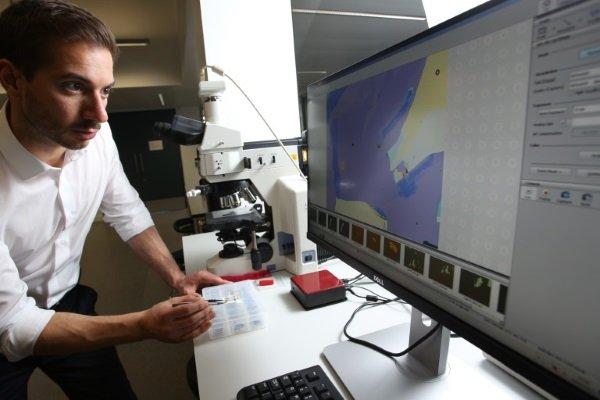 دکتر Oikonomou در حال مشاهده ورقه های گرافین از طریق میکروسکوپ