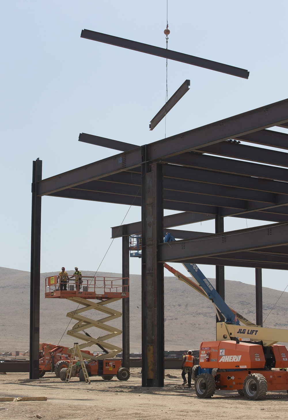 Support beams are lowered in to position during the construction of the new Tesla Motors Inc., Gigafactory, Tuesday, July 26, 2016, in Sparks, Nev. It's Tesla Motors biggest bet yet: a massive, $5 billion factory in the Nevada desert that could almost double the world's production of lithium-ion batteries by 2018. (AP Photo/Rich Pedroncelli)
