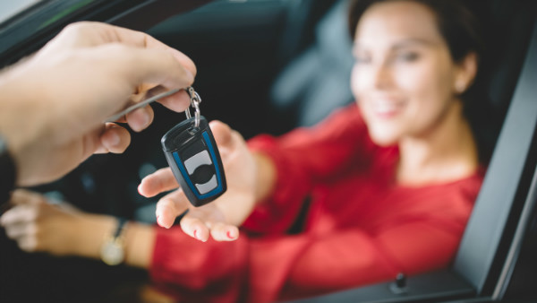 young-woman-sitting-in-new-car-and-taking-the-keys-from-the-1