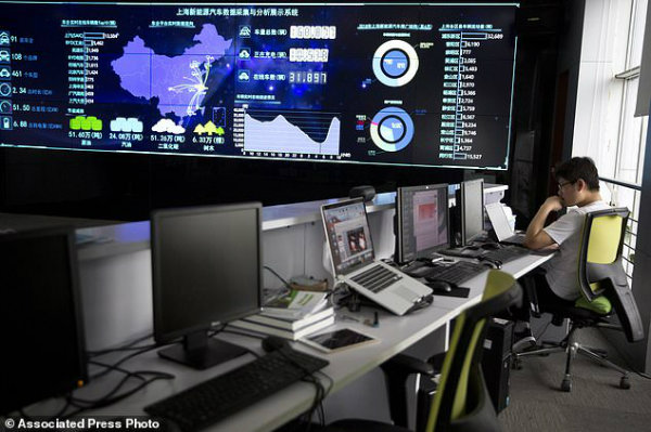 A staff member (pictured) looks at a laptop near a screen displaying live data from vehicles at the Shanghai Electric Vehicle Public Data Collecting, Monitoring and Research Centre